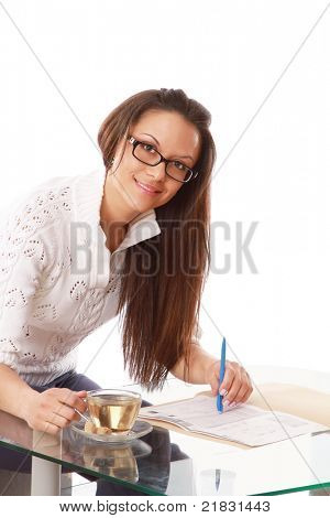 A woman with documents drinks tea at the desk - on white background