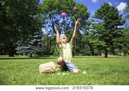 boy juggles with Easter eggs outdoor. the concept of Easter Egg Hunt