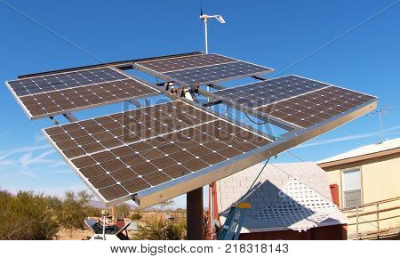 A solar module array and wind generator gathering energy for an Arizona house.