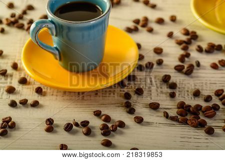 coffee cups with diferent colors with coffee beans liyng in the background
