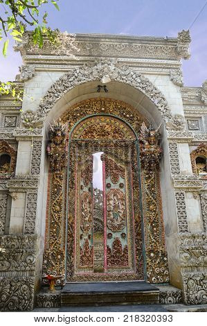 Arched white-stone temple entrance. Doors are ornately carved & painted. 2 demon gods protecting the entrance. Offerings on each side of the doors & on doorstep. Ubud Bali - September 2015