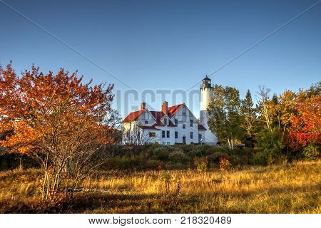 Michigan Autumn Lighthouse. The Point Iroquois Lighthouse framed by fall foliage on the coast of Lake Superior. Hiawatha National Forest. Brimley, Michigan, USA.