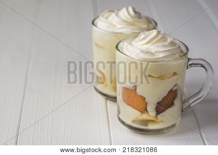 Two glass cups with banana pudding on a white table. Milk and banana dessert. The concept of dietary vegetarian diet.
