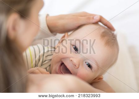 Baby breastfeeding. Mother holding her newborn child. Little kid boy laughing and looking at camera.