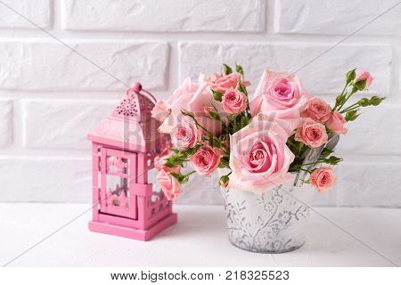 Bunch of tender pink roses flowers and decorative pink lantern against white brick wall. Floral still life. Selective focus. Place ffor text.