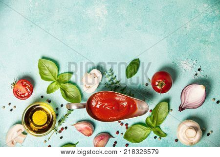 Fresh ingredients on blue stone background. Ingredients for cooking pizza, pasta sause, italian or vegetarian food. Top view, flat lay