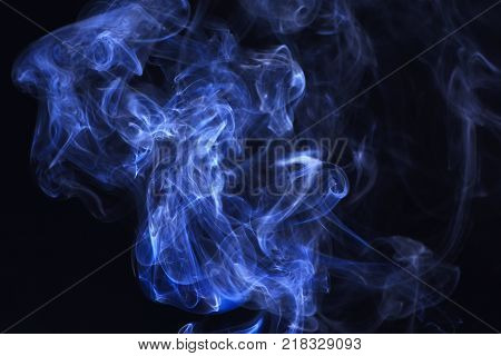 Blue ink in freeze motion powder splatted explosion. Spirit and ghost miracle. Blue smoke on black background. Smoking cloud backdrop. Abstract background with smoke.