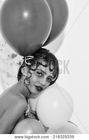 Pretty girl or cute woman with curly lock of hair hairstyle sexy rosy lips stylish makeup on smiling face with party balloons colorful pink hearts has bare shoulder isolated on white background