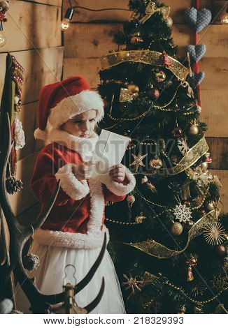 New year small girl with paper. Winter holiday and vacation. Xmas party celebration. Christmas happy child read wish letter. Santa claus kid at Christmas tree.