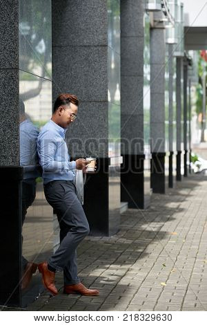Businessman standing outside the office building, drinking coffee and checking smartphone