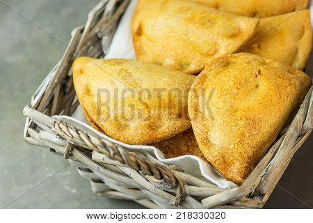 Home Baked Empanadas Turnover Pies with Pisto Vegetable Cheese Filling in Tomato Sauce in Wicker Basket. Spanish Pastry. Dark Concrete Stone background. Top View Minimalist