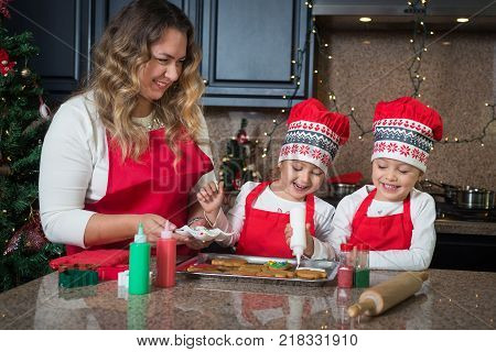 Mom and twin girls in red aprons and hats making Christmas cookies together in modern kitchen, laughing. Baking with kids.