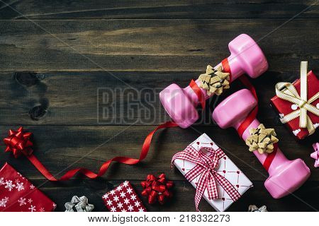 Pink Sport Dumbbells And Gift Bow On White Wooden Background, Merry Christmas And Happy New Year Wis