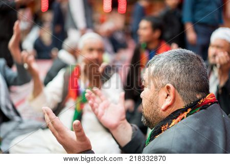 Muslim people praying together with hands up