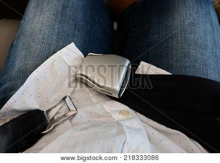 top view of unlocked airplane seat belt over passenger lap