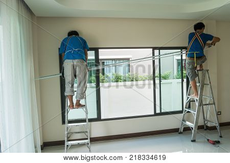 Handy man home Installation and repair service technician or home owner hanging curtains for the window treatment in a new house.