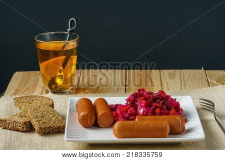 Boiled Sausages with salad on a plate a glass of tea austere breakfast