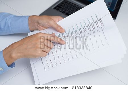 Marketing analyst working with data and examining list. Close-up of businesswoman reviewing report and reading information. Business paper concept