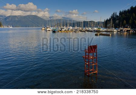 A red lifeguard chair stands in the water at Deep Cove North Vancouver Canada.