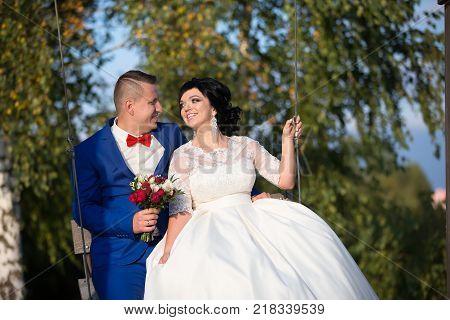 Belarus Gomel September 29 2017 Wedding Feast.The bride and groom on the swing.The bride and groom on a walk