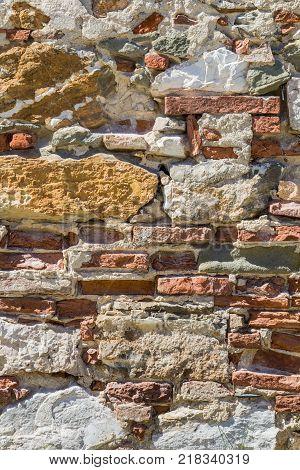 Exposed bricks through the plaster on a deserted farmhouse in Pisa