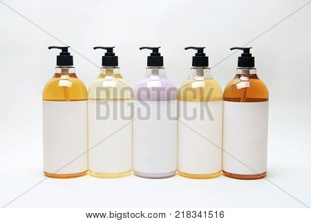 Set of different bottles for beauty hygiene and health on a white background with reflection they shampoo conditioner and other hair products