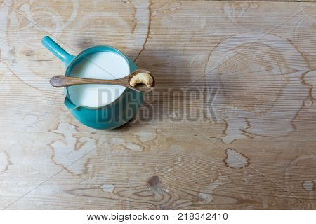 Side handle ceramic bowl pitcher of cashew milk with wooden spoon and single cashew on antique wood background space for text horizontal aspect