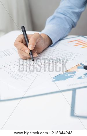 Female manager learning business papers and making correction in paper. Close-up of banking specialist analyzing list of client. Paperwork concept