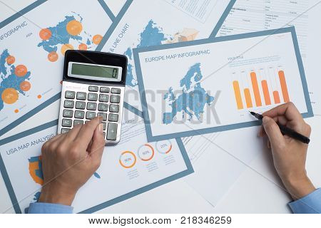 Business analyst doing paperwork using calculator for audit. Close-up of businesswoman looking through documents. Finance concept