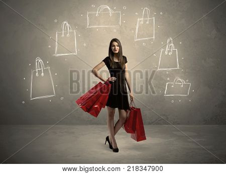 A beautiful young girl in black standing with red shopping bags in front of brown background wall and drawing illustration concept