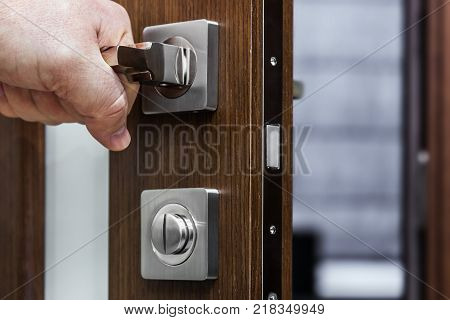 hand holds and opens a door handle on veneer doors