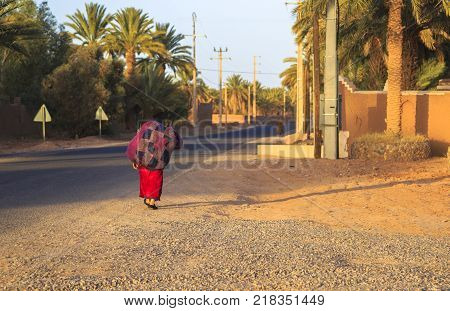 M'hamid Morocco - February 22 2016: Rear view of unidentified woman carrying jute burlap sack during evening