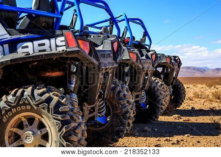 Merzouga Morocco - Feb 21 2016: Close-up of wheel of Blue Polaris RZR 800 aligned and stationed with no pilot in Morocco desert near Merzouga. Merzouga is famous for its dunes the highest in Morocco.