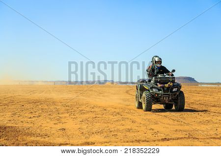 Ait Saoun Morocco - February 22 2016: Man riding atv quad bike on sand in desert on a sunny day in Ait Saoun desert in Morocco.