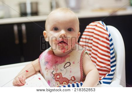 Girl toddler is eating soup in high chair splashing around herself. Playing with food and learning to eat concept.  Dirty face of happy kid. Portrait of a baby eating with a stained face