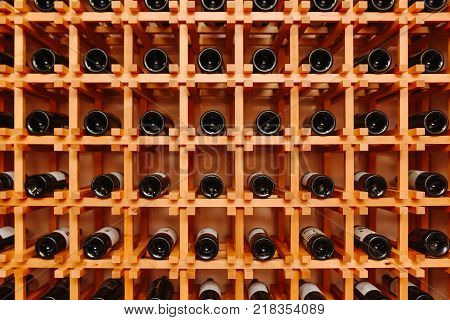 The bottles on the shelves of the wine cellar. Front view