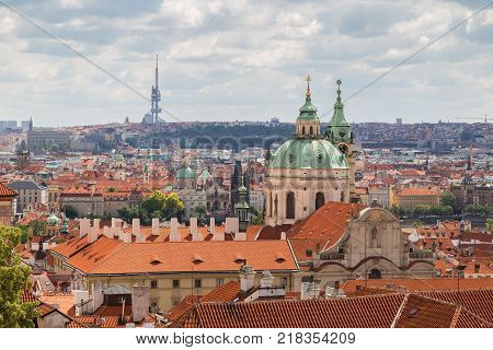 Scenic view of the St. Nicholas Church, other old buildings at the Mala Strana District (Lesser Town) and beyond in Prague, Czech Republic. Viewed slightly from above in the daytime.