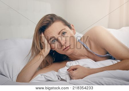 Attractive middle-aged blond woman lying propped up in bed staring intently at the camera with a serious expression