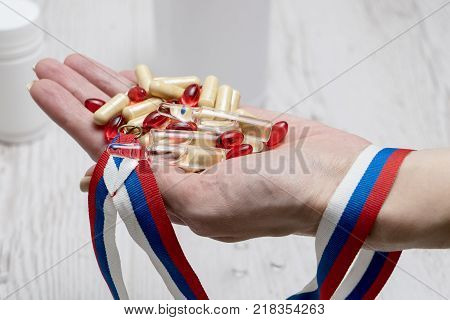 tablets red pills and syringe of doping drugs or medicine with russian tape flag in the hand poster