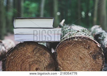A stack of books lying on felled trees save trees - read ebooks concept