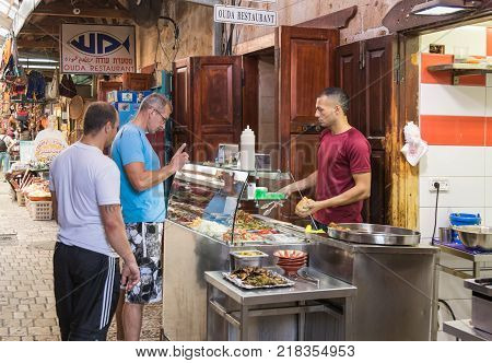Acre Israel November 03 2017 : The seller sells the clients to the shawarma on the market in the old town of Acre in Israel