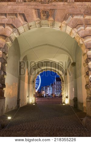 Cobblestone street and lit gateway at the historic Green Gate at the Main Town in Gdansk, Poland, in the evening.