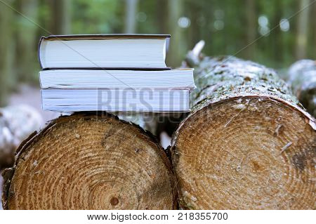 A stack of books lying on felled trees save trees - read ebooks