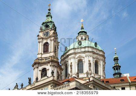View of tower and dome of Church of Saint Nicholas (St. Nicholas Church) in Mala Strana or Lesser Town in Prague, Czech Republic, in the daytime.