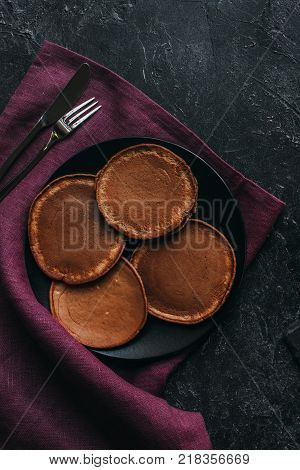 top view of plate of chocolate pancakes with cutlery on red napkin