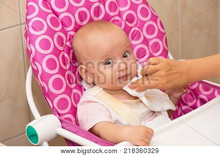 Mother wipes babys mouth with white napkin