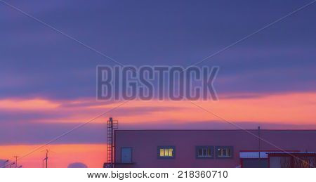 Blurred violet sky background - top of an industrial building against the sunset.
