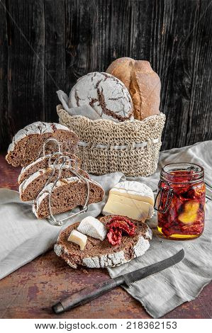 Bread whole wheat leavened handmade cheese and sun-dried tomatoes. The vertical frame.