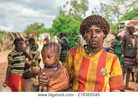 TURMI, OMO VALLEY, ETHIOPIA - MAY 5, 2015: Portrait of a woman from the Hamar tribe with her baby in south Ethiopia. Married hamar women apply red clay to their hair and fashion it into long tufts.