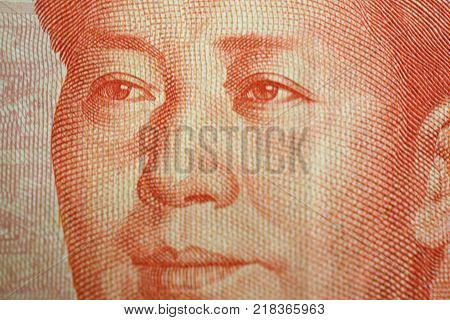 Macro detail of a Chinese one hundred rmb note bill showing the face portrait of Mao Zedong